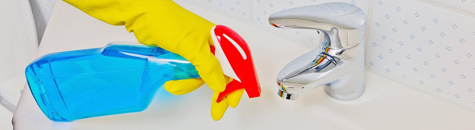 Eine Person putzt mit Gummihandschuhen und Putzmittel ein Waschbecken.
