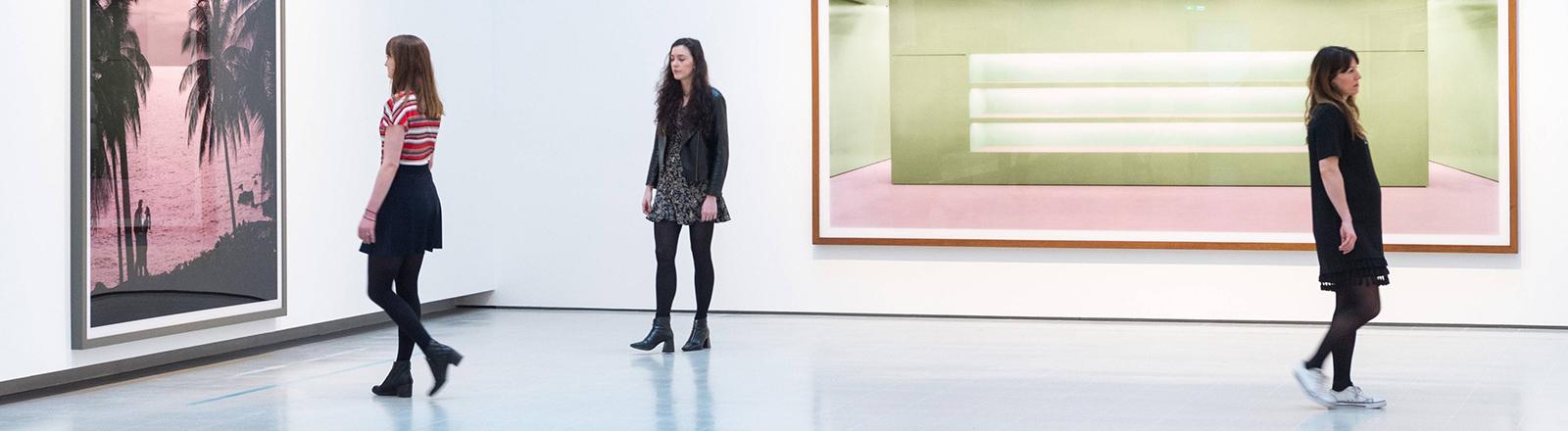 Eine junge Frau sitzt vor dem Bild des Fotokünstlers Andreas Gursky.