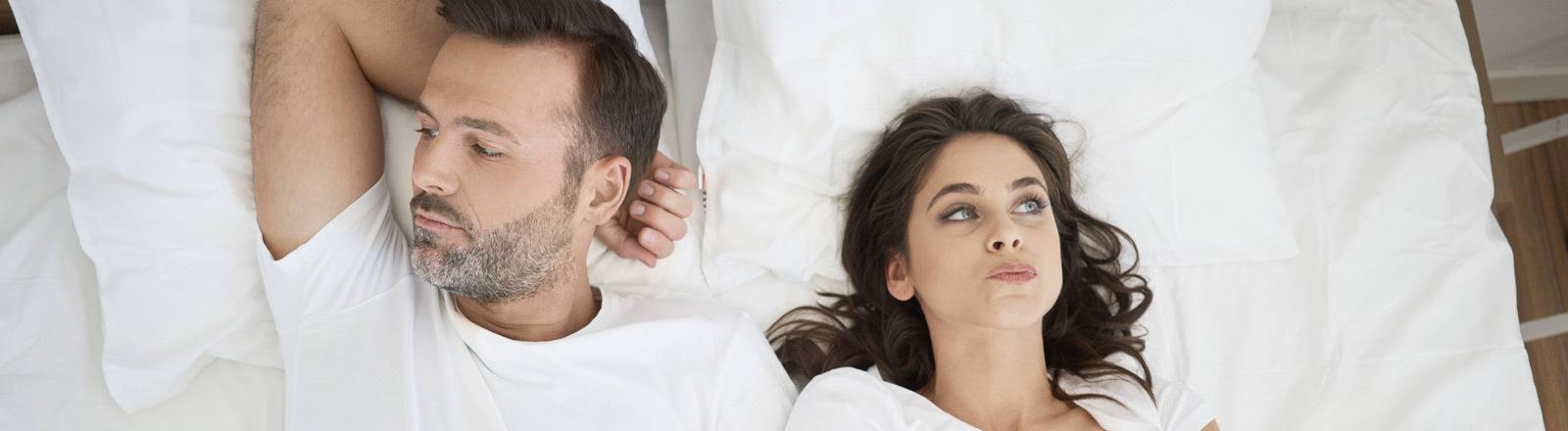 Ein Paar liegt offensichtlich gefrustet im gemeinsamen Bett.