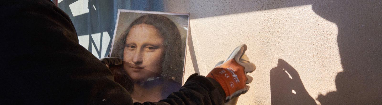 Der Künstler Tank steht auf dem Gerüst hoch oben, gegenüber der East-Side Gallery. Er hält eine Vorlage von Da Vincis Mona Lisa in der Hand, um das Werk aus dem Pariser Louvre so getreu wie möglich an die fensterlose Hausfassade des East Side Hotels zu übertragen.