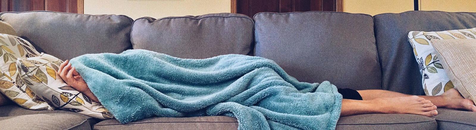 Ein Mensch liegt krank auf der Couch und hat sich unter einer warmen Decke verkrochen.