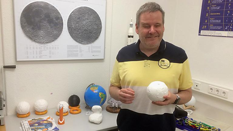 Gerhard Jaworek mit einem Planetenmodell in seiner Hand.