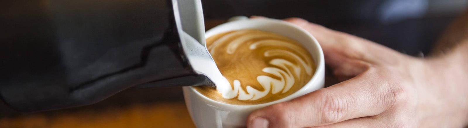 Männliche Hand schüttet geschäumte Milch aus einer Kanne in eine Tasse mit Kaffee.