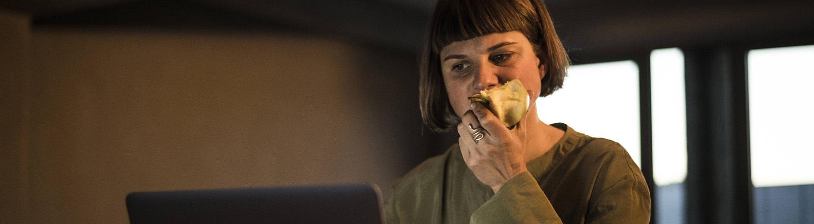 Eine Frau sitzt am Laptop und isst einen Apfel