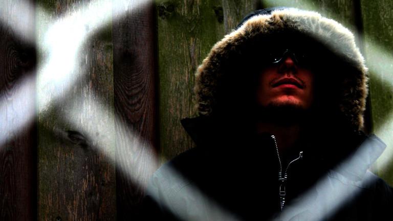 Ein Mann mit Sonnenbrille und Kapuze steht hinter einem Maschendrahtzaun.