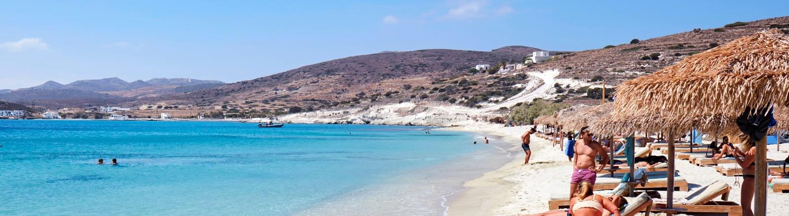 Zu sehen ist blaues Meer und heller Sand an der Küste der griechischen Insel Kimolos.