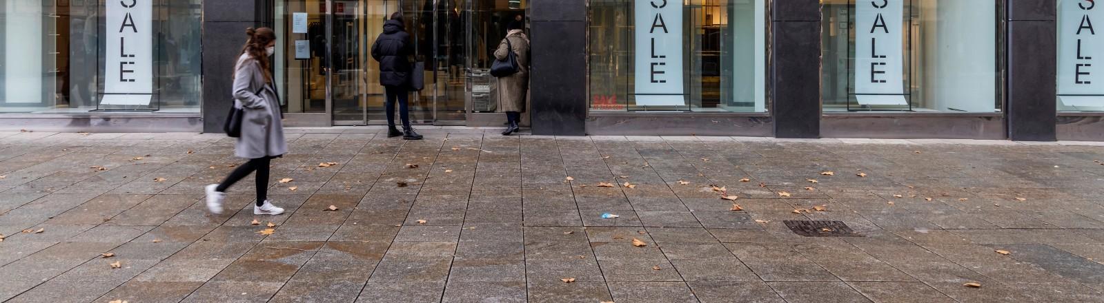 Eine Frau läuft mit einem Mund-Nasen-Schutz durch eine leere Fußgängerzone.
