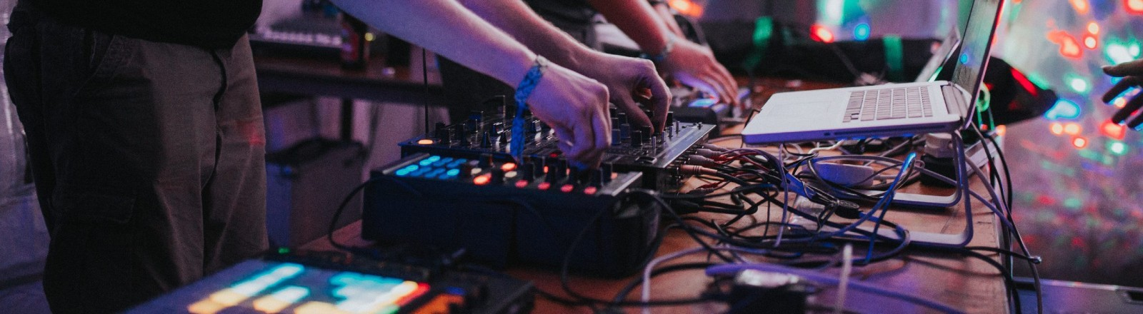 """DJ-Set auf der Demoparty """"Evoke"""" 2019, bei dem im Hintergrund ein Demo zu sehen ist."""