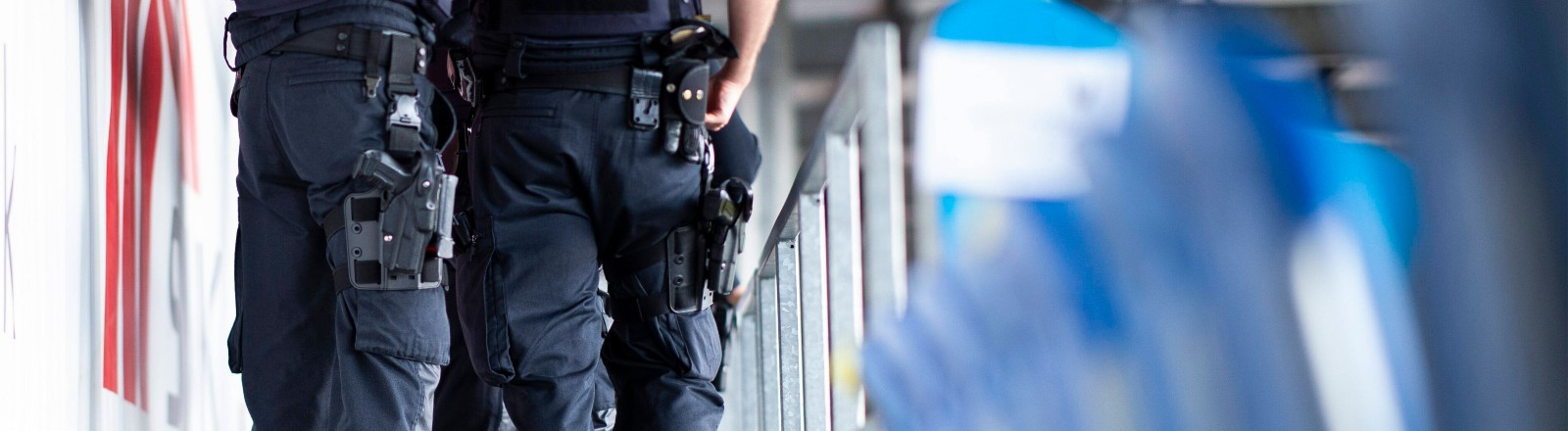 Polizistinnen und Polizisten sind auf der Tribüne in einem leeren Fußballstadion.