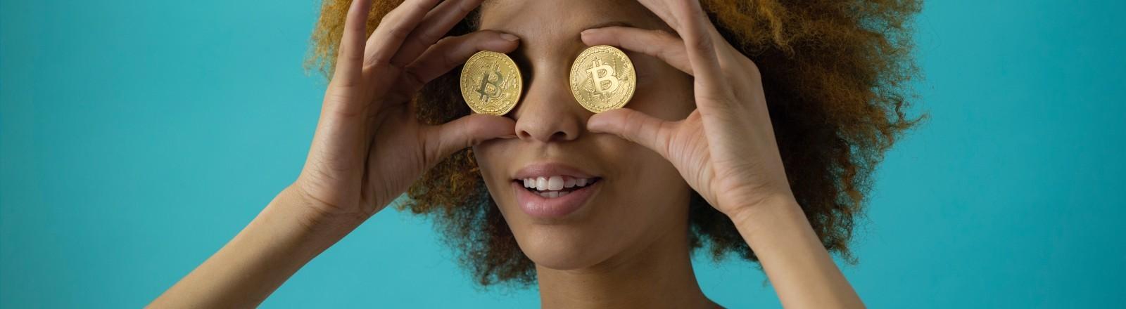 Eine Frau hält Bitcoin-Münzen vor ihre Augen.