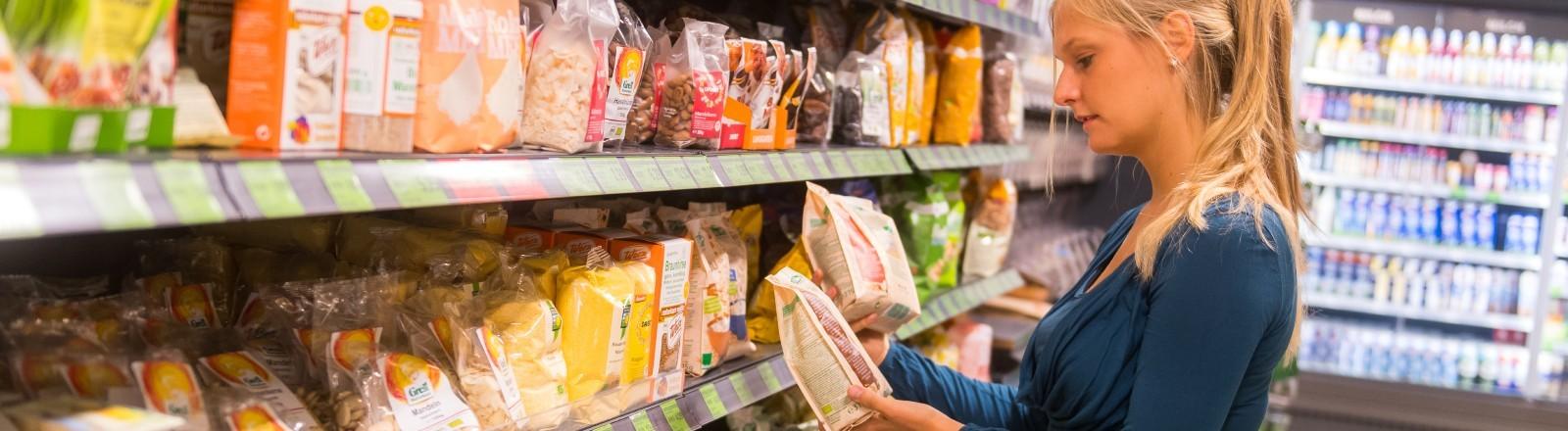 Eine Frau ist in einem Supermarkt und schaut auf die Zutaten eines Lebensmittel.