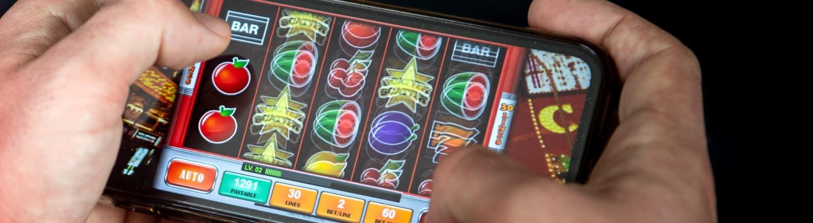 Ein Mann spielt en Glücksspiel auf seinem Smartphone im Netz.