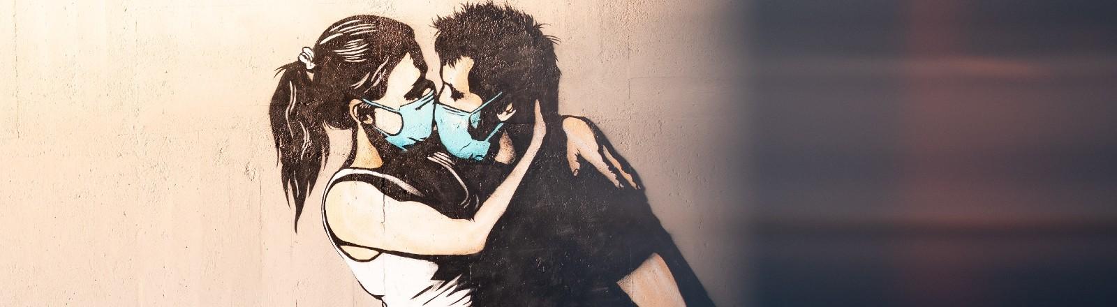 Eine Zeichnung an einer Wand zeigt ein Paar, das sich mit Mund-Nasen-Schutz küsst.