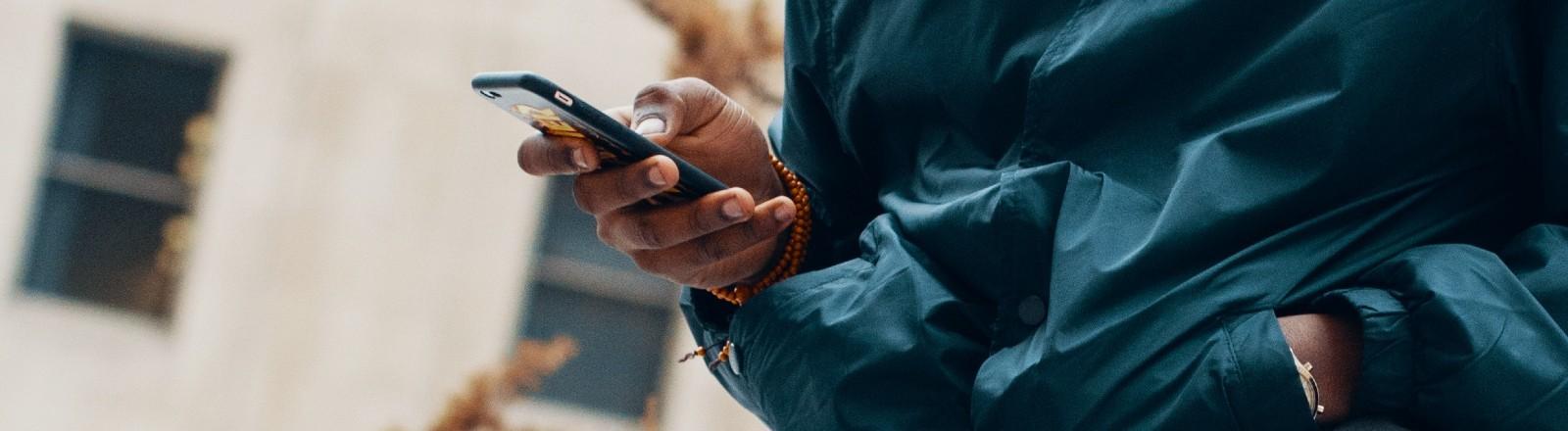 Ein Mann sitzt draußen und schaut auf sein Smartphone.
