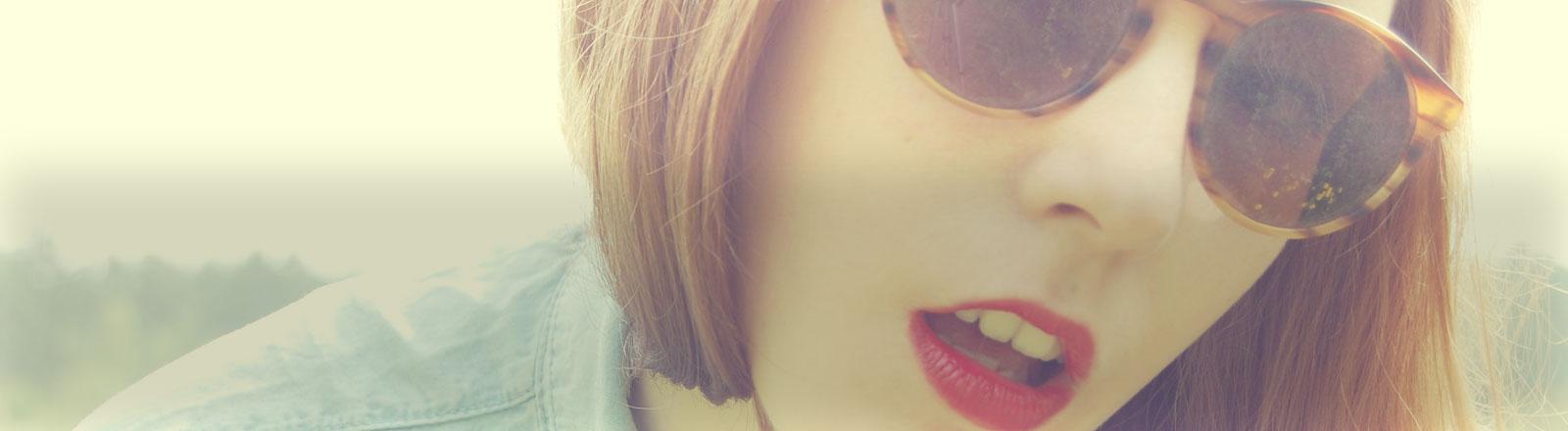 Eine Frau mit großer Sonnenbrille schaut in die Kamera.