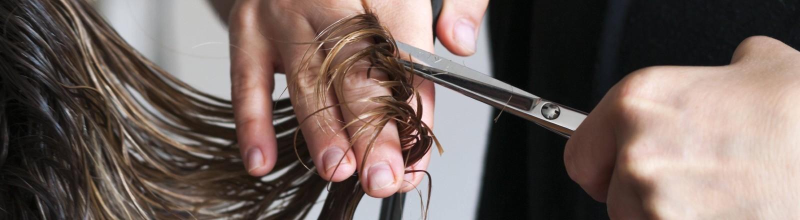 Eine Friseurin schneidet einer Person mit langen Haaren die Haarspitzen.