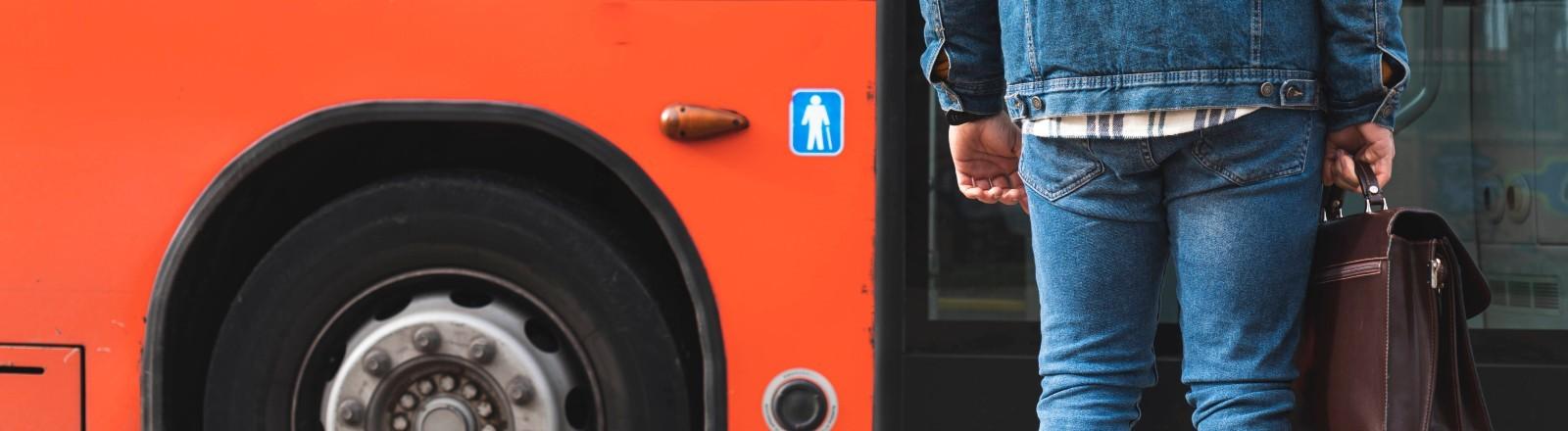 Ein Mann steht vor einer Bustür.