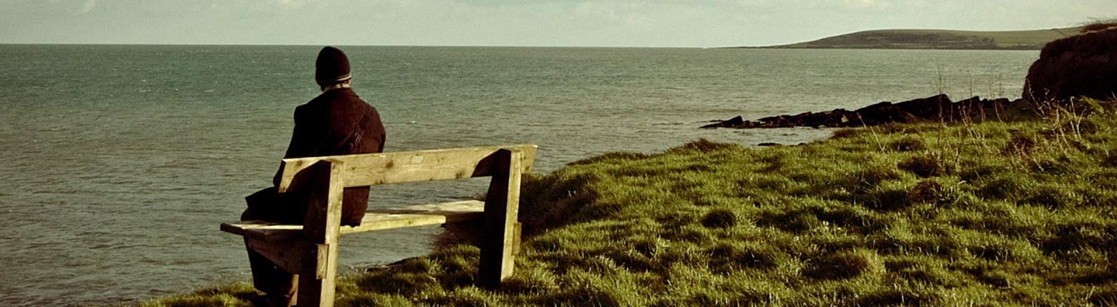 Ein Mann sitzt auf einer Bank und schaut aufs Meer