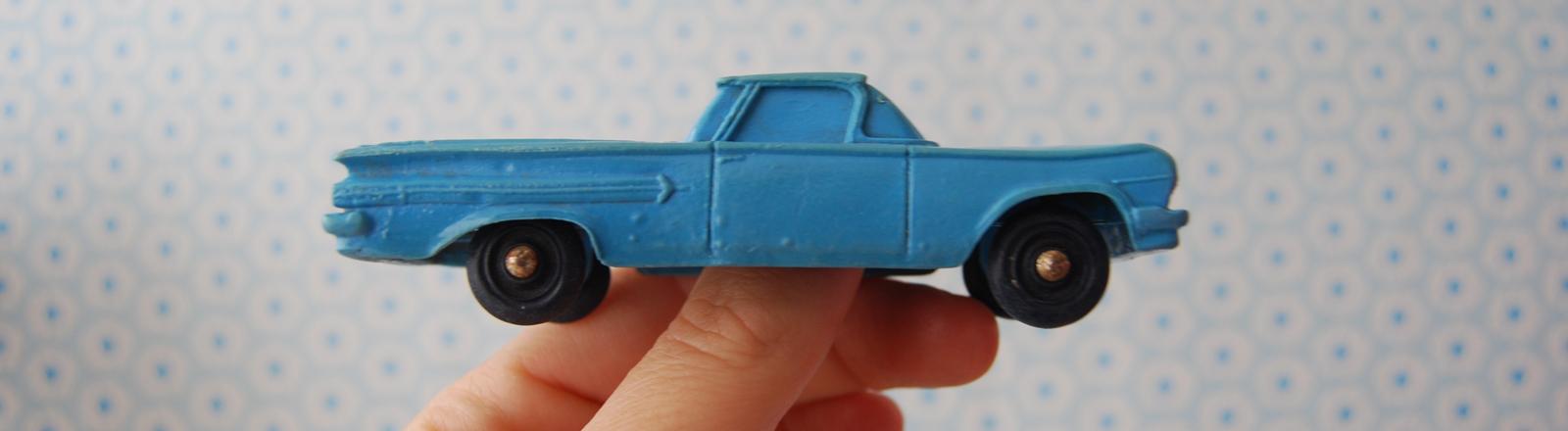 Eine Frau oder Mann hält ein Spielzeugauto in den Händen.