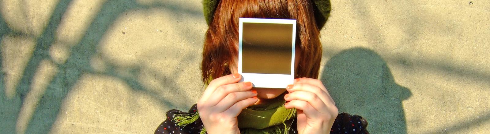 Frau mit Polaroid-Foto vor dem Gesicht