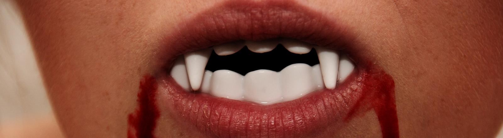 Nahaufnahme von einem blutverschmierten Mund mit Vampirzähnen