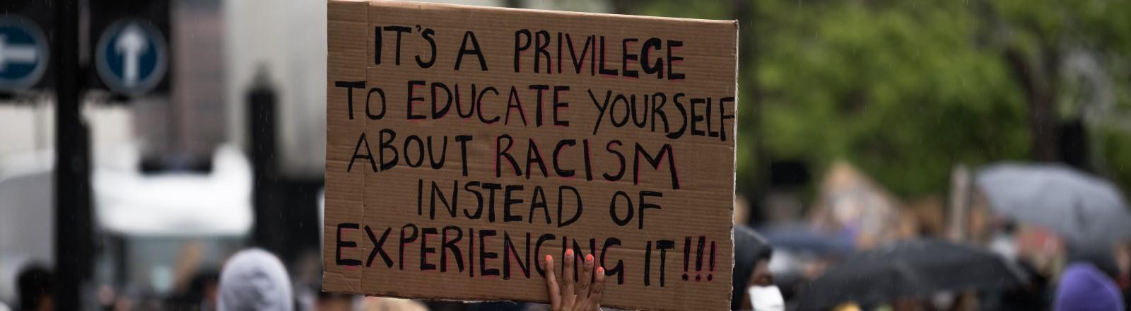 Eine Frau auf einer Black-Lives-Matter-Demo hält ein Schild hoch, das Rassismus verdeutlich.