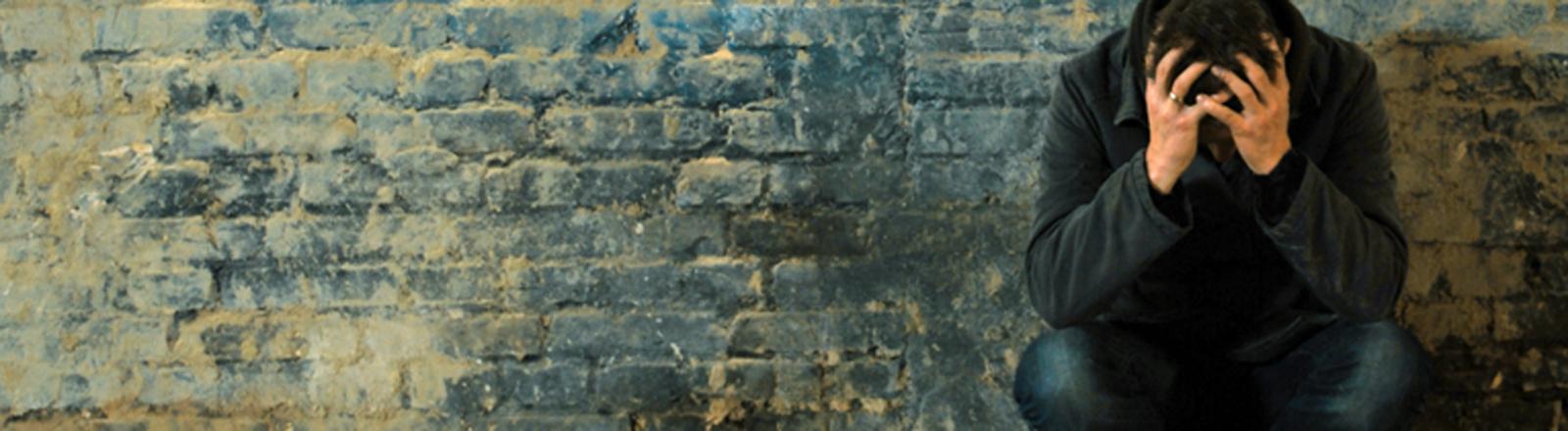 Ein Mann kniet an einer Wand und stützt den Kopf in seine Hände.