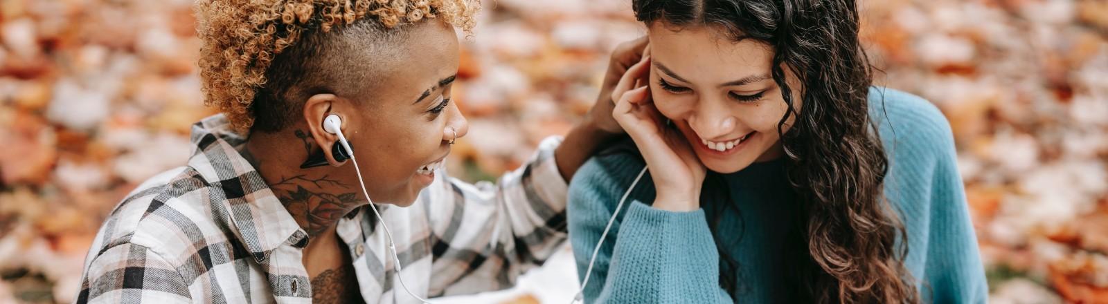 Zwei Frauen teilen sich einen Kopfhörer und spielen etwas von ihrem Smartphone ab.