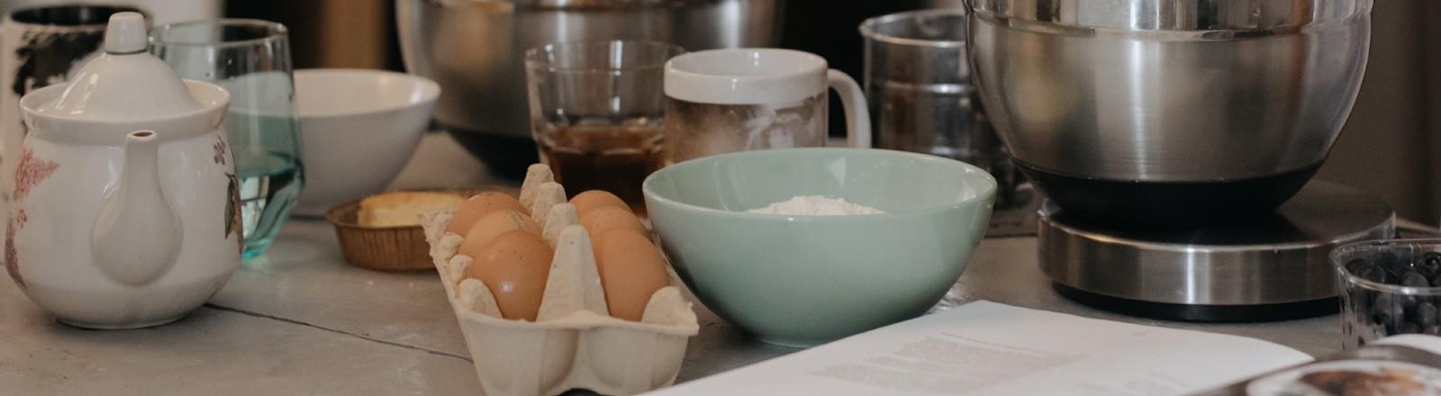 Ein Kochbuch liegt zusammen mit Zutaten in einer Küche.