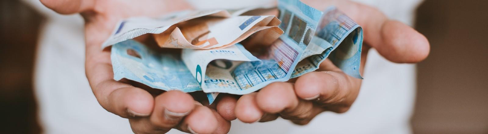 Mann hält Euroscheine in seiner Hand.