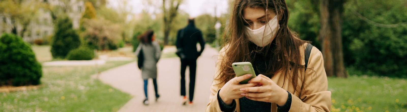 Eine Frau mit Mund-Nasen-Schutz schaut auf ihr Smartphone.