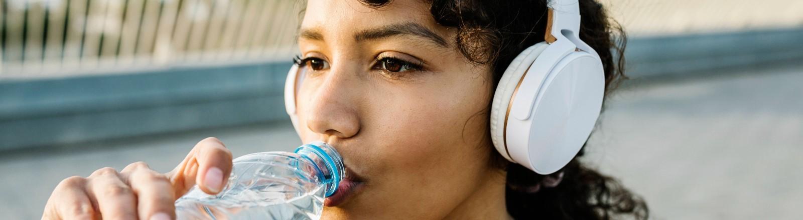 Eine Frau trägt Kopfhörer und trinkt aus einer Flasche.