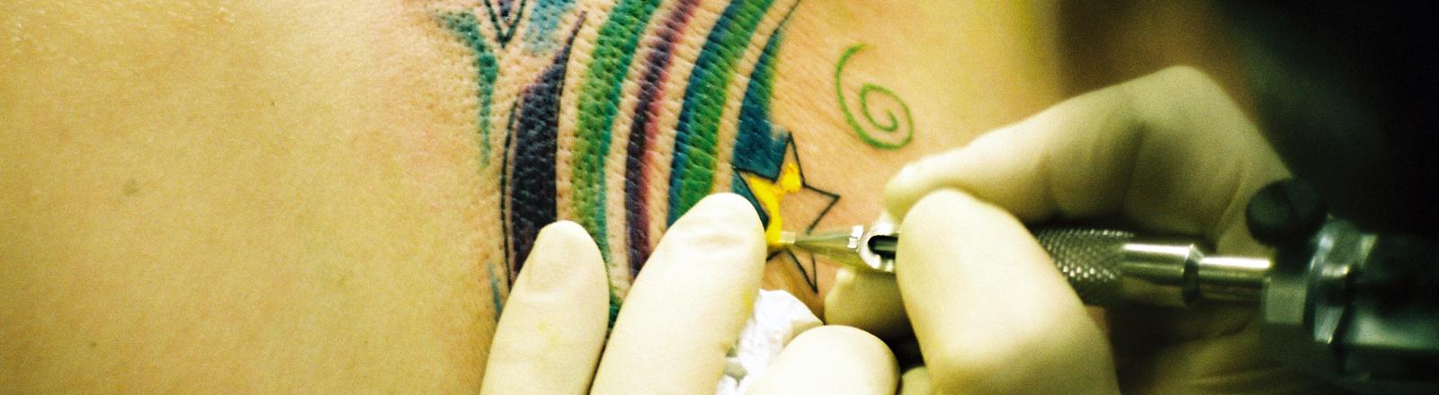 Tätowierer beim Stechen eines Sterns.