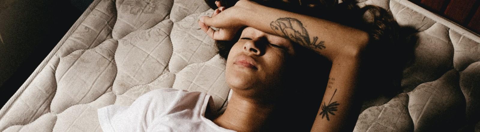 Frau liegt auf einer Matratze und hält sich ihren Arm gegen ihre Stirn