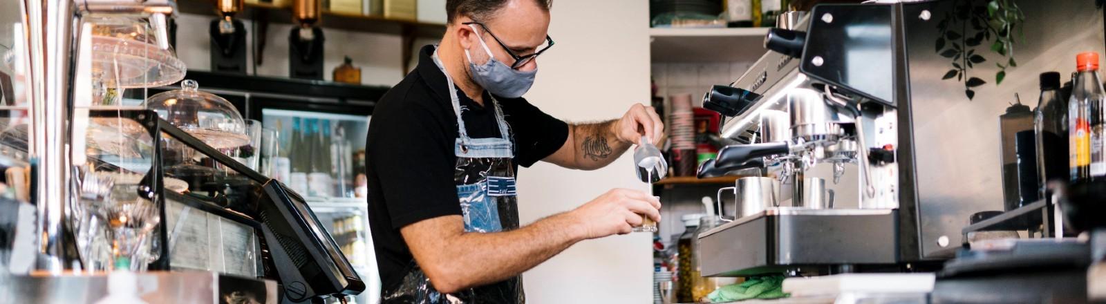 Ein Barista steht in einem Café hinter der Theke und bereitet einen Kaffee zu