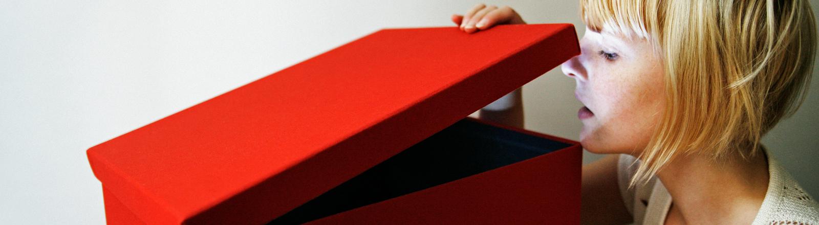 Frau schaut in eine Kiste
