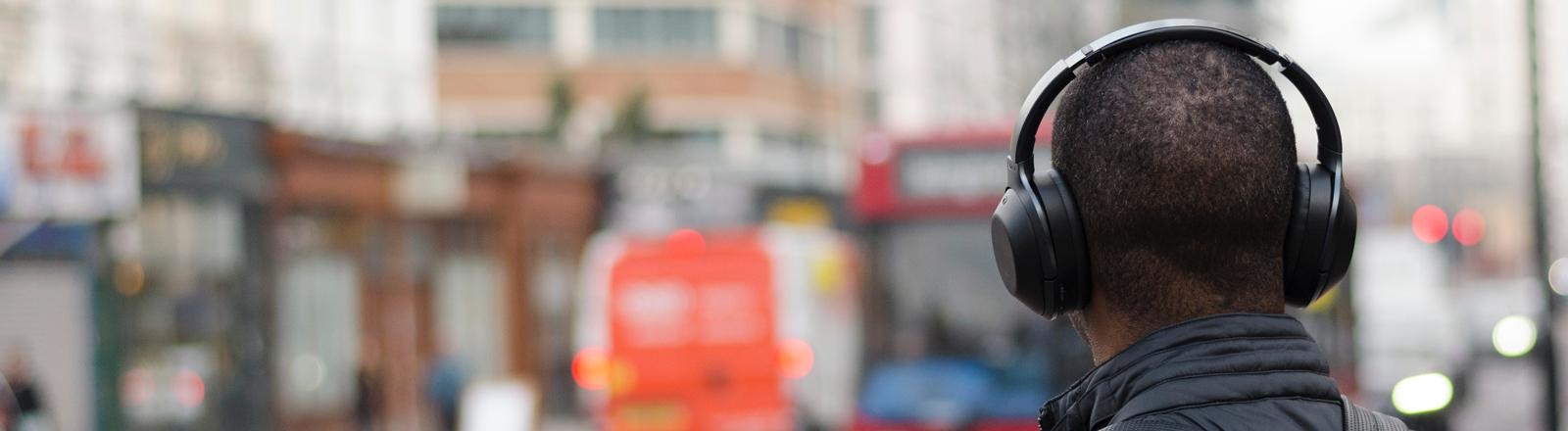 Mann mit Kopfhörern im Straßenverkehr