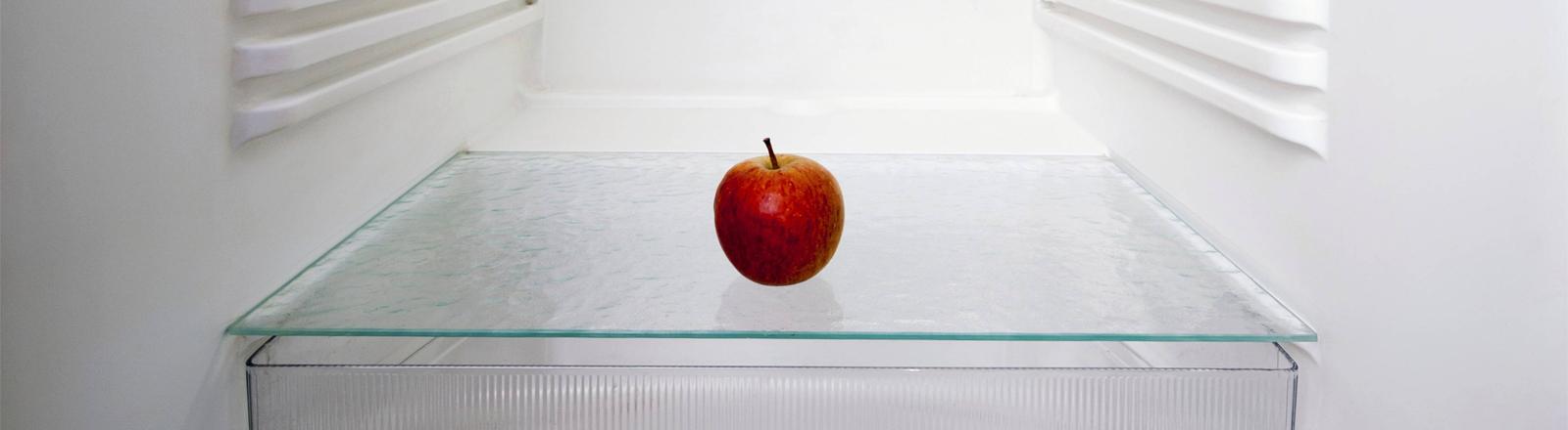 Ein Apfel liegt in leerem Kühlschrank