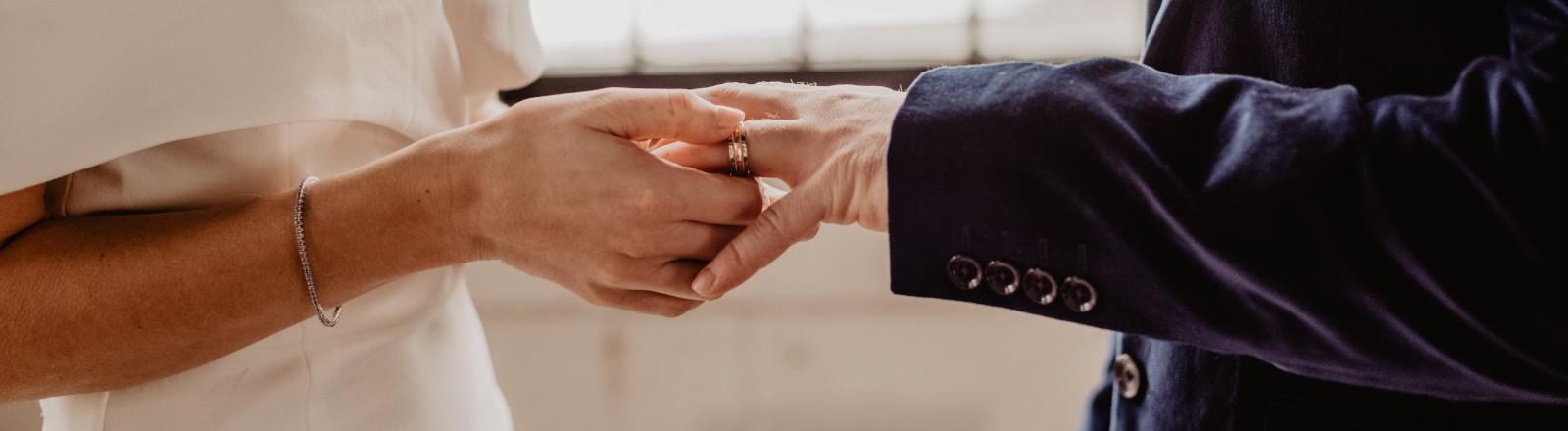 Eine Braut steckt ihrem Bräutigam den Ehering an den Finger.