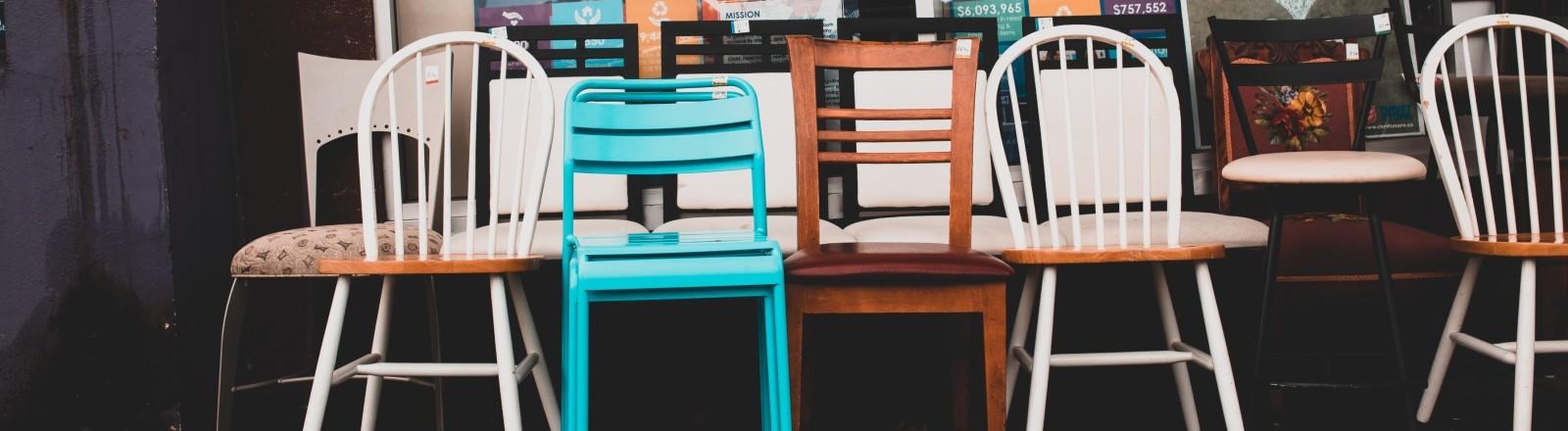Gebrauchte Stühle stehen vor einem Laden zum Verkauf.