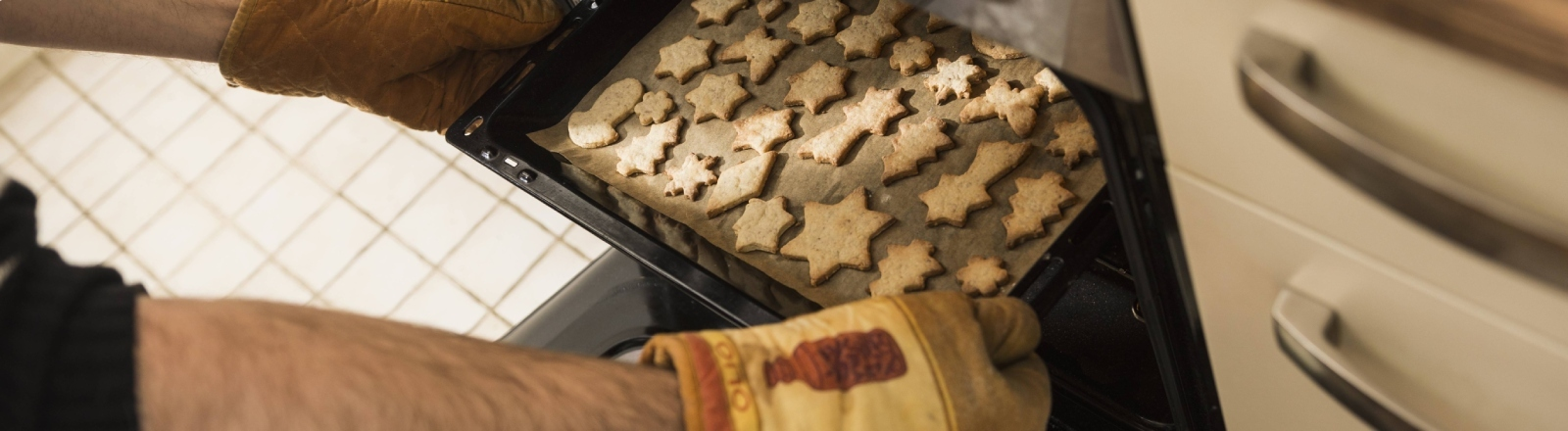 Ein Blech voller Sterne: fertige Plätzchen werden aus dem Ofen geholt