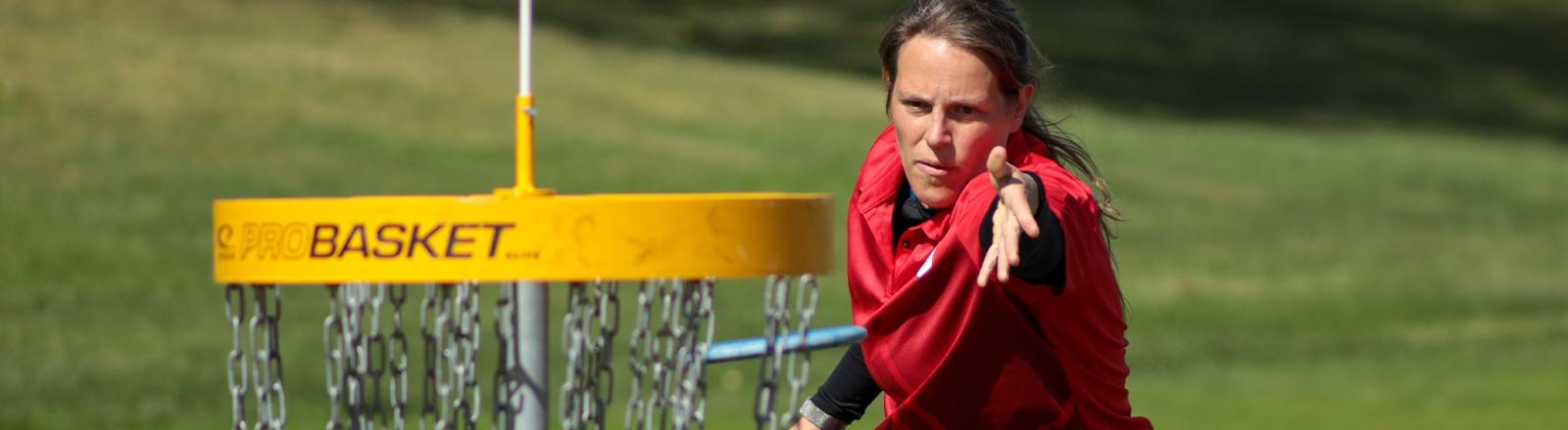 Antonia Faber wirft eine Frisbee in einen Korb