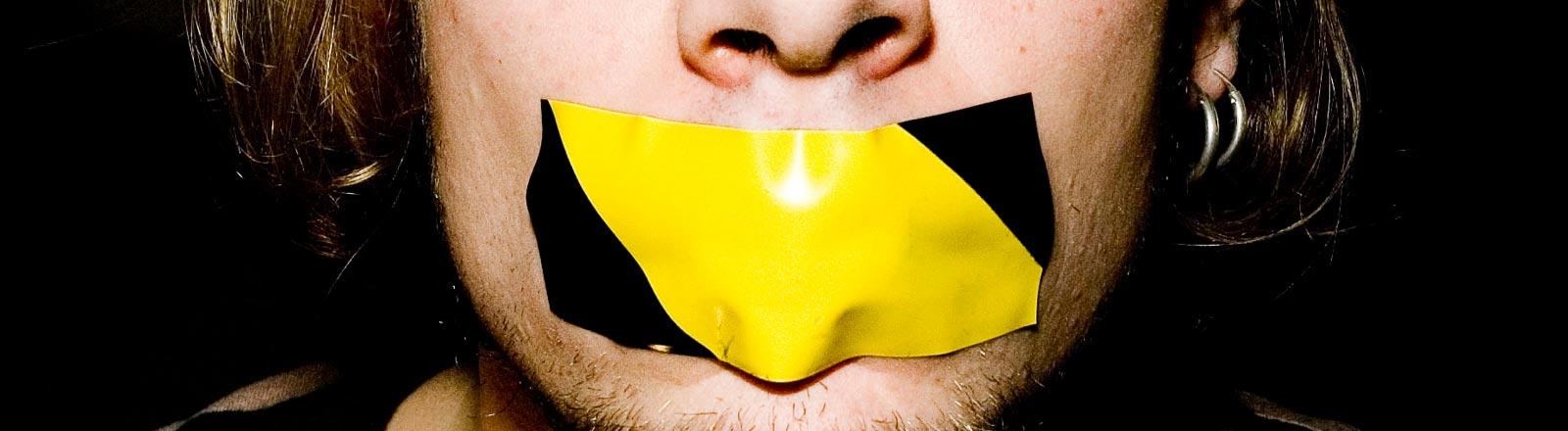 Ein Mann hat den Mund mit Klebeband zugeklebt bekommen.