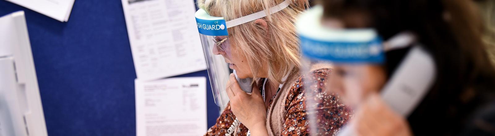 Mitarbeiter des Gesundheitsamtes Berlin Mitte telefonieren mit Gesichtsschutzvisier.