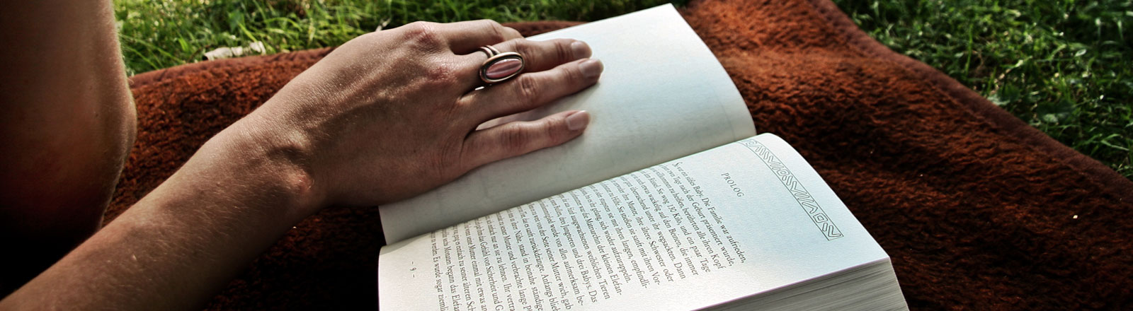 Eine Frau liest ein Buch auf einer Wiese.