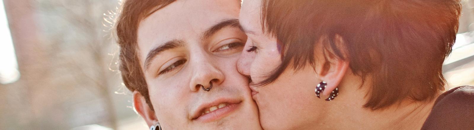 Eine Frau küsst mit geschlossenen Augen einen Mann auf die Wange, er schaut sie an.