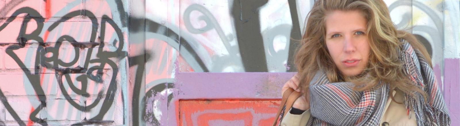 Greta Taubert steht vor einer Wand mit Graffiti.