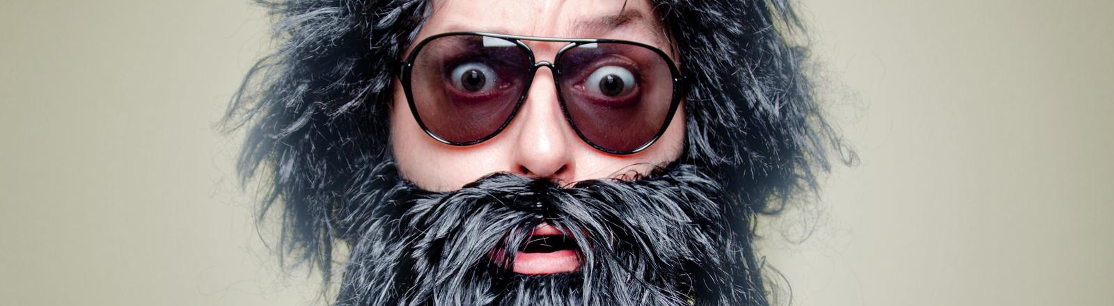 Ein Mann mit Bart und Perücke hat die Augen weit aufgerissen, er trägt eine Sonnenbrille.