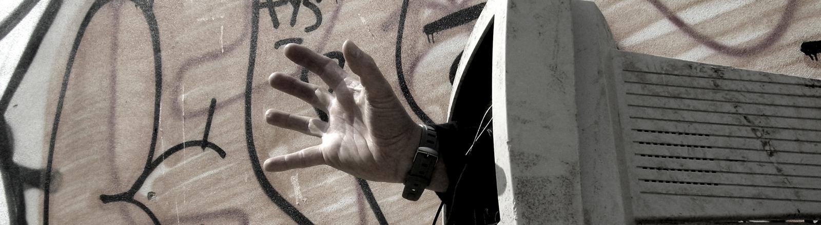 Eine Hand greift gierig aus einem defekten Computergehäuse.