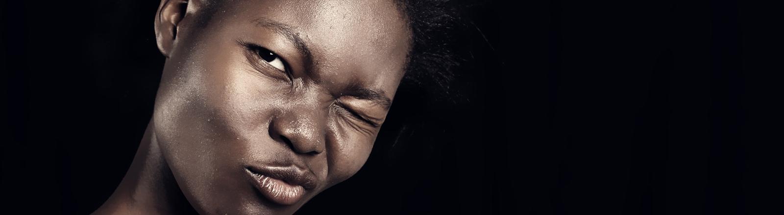 Eine junge Frau mit dunkler Hautfarbe kneift das Auge zusammen.